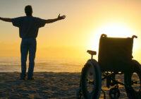 worshipping man standing next to empty wheelchair