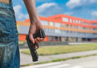 person with gun outside a school